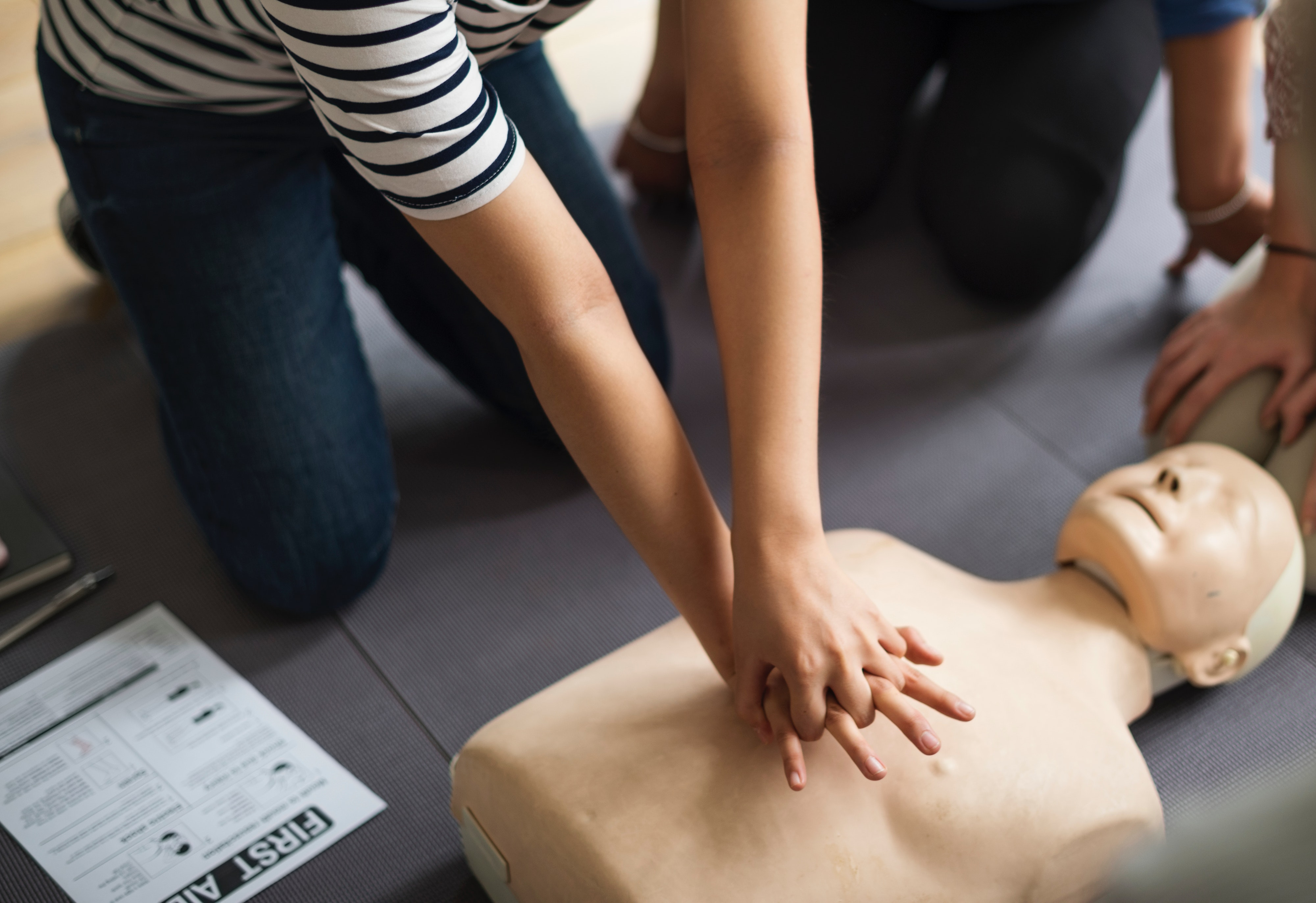 Person performing CPR on a dummy
